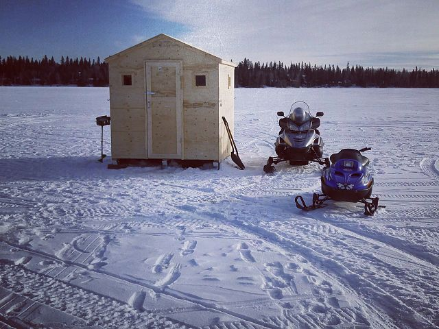The sleds resting by the ice fishing shack