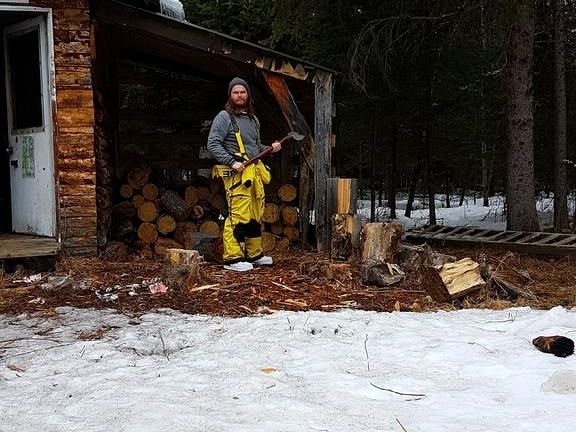 Local handsome lumberjack splitting wood to leave for the next group of riders to enjoy.